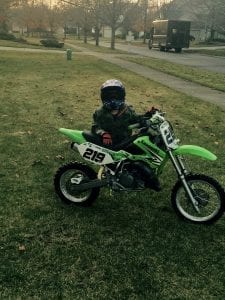 a child with a dirt bike on the front lawn in Bloomfield