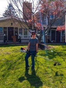 Lawn care provider holding weed whip on Philadelphia front lanw