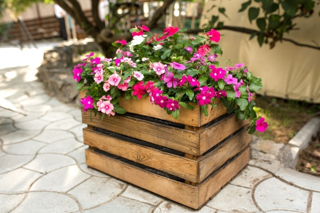 A flower bed with beautiful pink and red flowers built by a LawnGuru Pro