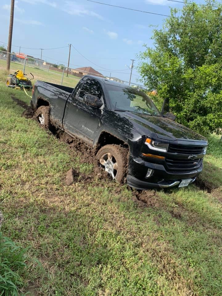 Chevrolet truck and John Deere Mower stuck in the mud