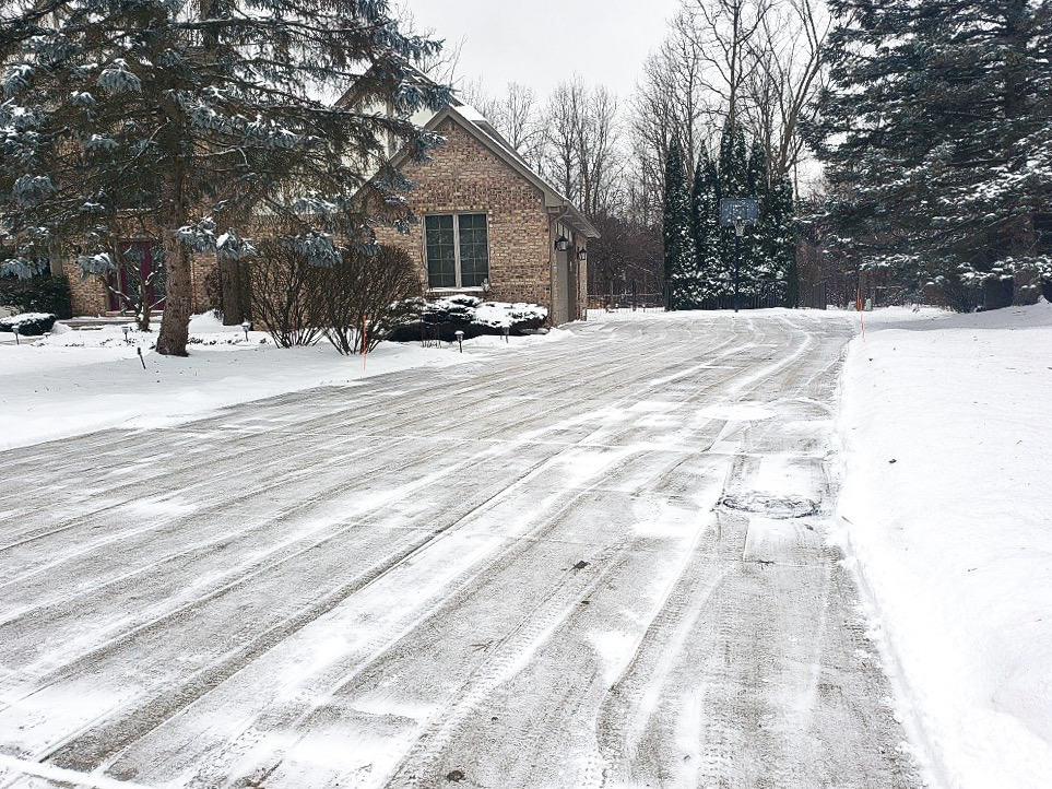A driveway freshly plowed after a heavy snowfall in Michigan