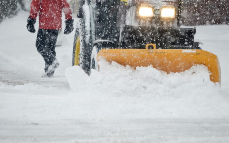 Person walking during heavy snowfall with tractor Plowing streets during snow storm winter