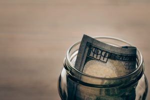 glass jar with dollar banknote on wooden tabletop